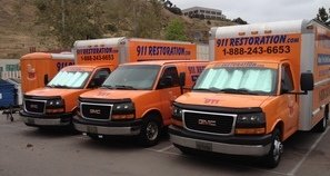 Water and Mold Damage Restoration Vans And Trucks At Job Site